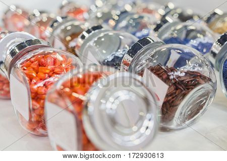 Colorful pills in the glass bottles - chemistry and pharmaceutical concept, close up