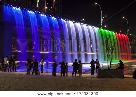 DUBAI UAE - NOV 28 2016: Colorful illuminated Waterfall in Dubai. The Waterfall is part of the Dubai Water Canal development. United Arab Emirates Middle East