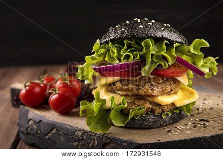 Vegan black burger with two chickpea cutlets, tomatoes, cheese, onion and salad on wooden table, dark background.