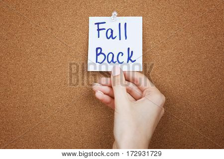 Female hand holding note with phrase FALL BACK on cork board background