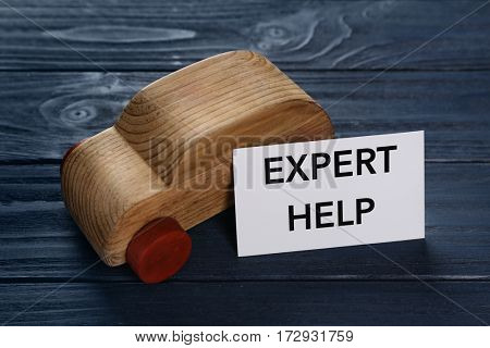 Phrase EXPERT HELP and toy car on wooden background