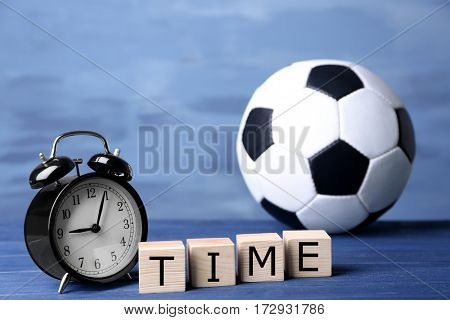 Alarm clock, cubes with word TIME and soccer ball on color background