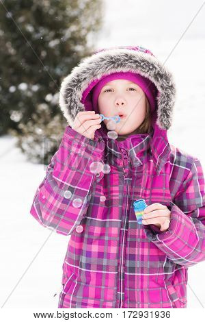 Little girl playing outdoors in snow blowing bubbles