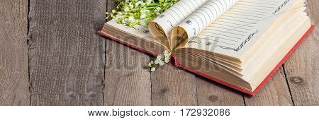 Book pages folded into a heart and a flower lily of the valley on the old wooden table. Soft focus deliberate slight blurring .