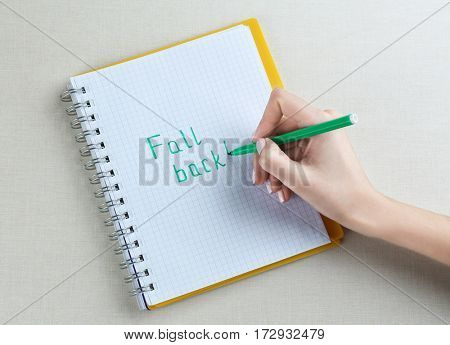 Female hand writing phrase FALL BACK in notebook