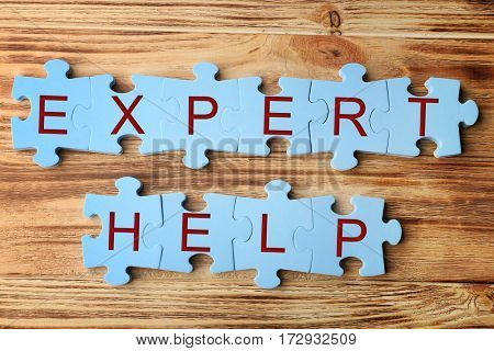 Phrase EXPERT HELP made of puzzle pieces on wooden background