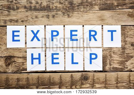 Phrase EXPERT HELP on wooden background