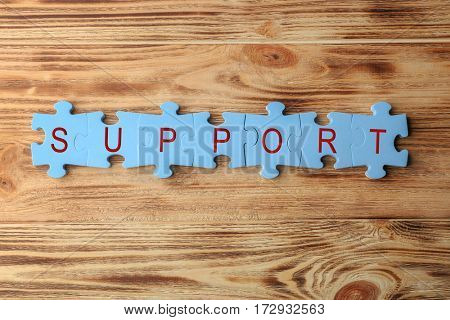 Word SUPPORT made of puzzle pieces on wooden background