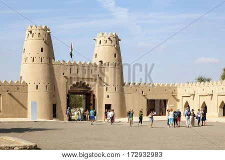 AL AIN UAE - NOV 29 2016: Group of tourists visiting the historic Al Jahlili fort in the city of Al Ain. Emirate of Abu Dhabi United Arab Emirates