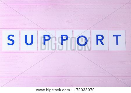 Word SUPPORT on color wooden background