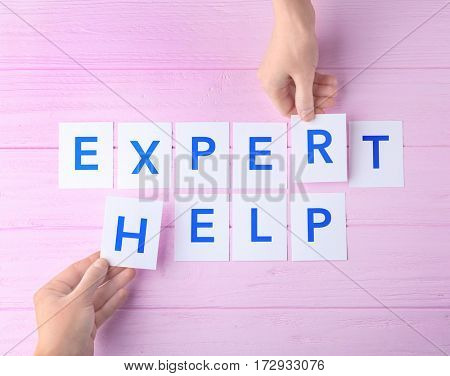 Female hands and phrase EXPERT HELP on wooden background