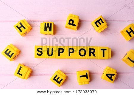 Word SUPPORT on wooden background