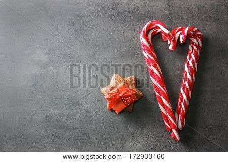 Sweet candy canes and present box on grey textured background