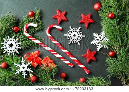 Christmas composition with candy canes and decorations on dark background