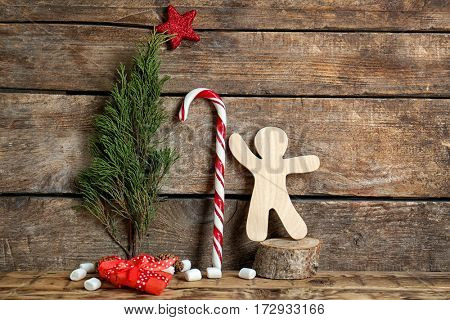 Christmas composition with candy cane and decorations on wooden background