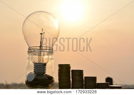 light bulbs and stack coins idea concept and silhouette style on road and under the sky