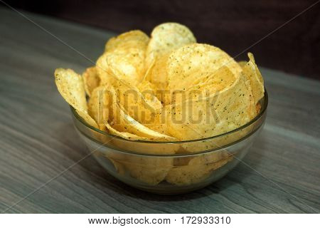 potato chips in a bowl on a wooden table