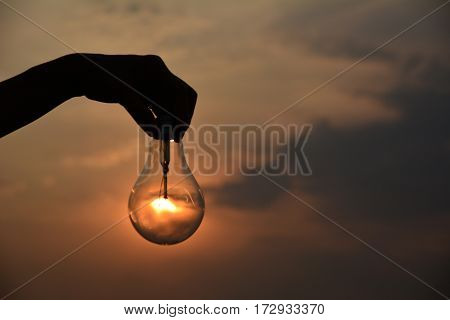 hand holding light bulbs idea concept and silhouette style under the sky