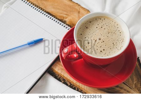 Cup of Hot Cappuccino Croissant and Chocolate in the Bed Empty Notebook for Note. Selective Focus. Copy space.