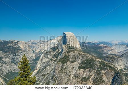 Half Dome is a granite dome at the eastern end of Yosemite Valley in Yosemite National Park California. It is a well-known rock formation in the park named for its distinct shape. One side is a sheer face while the other three sides are smooth and round m