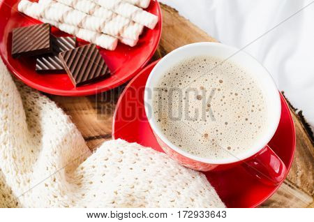 Breakfast in Bed. Tray with Cappuccino and Chocolate on a Bed with Plaid in Bedroom Interior. Selective Focus.