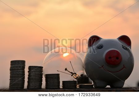 light bulbs and stack coins idea concept and silhouette style under the sky