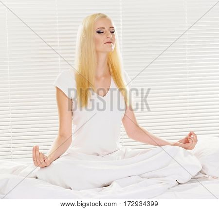 Good-looking blonde in white pajamas at home on a white background