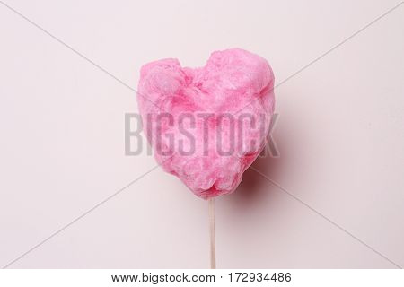 Sweet cotton candy in heart shape on light background