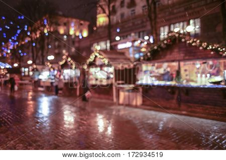 Christmas fair in city at night, blurred background