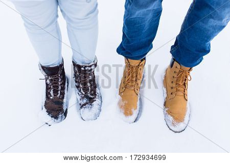 Legs and feet of couple in love in stylish shoes standing in snow