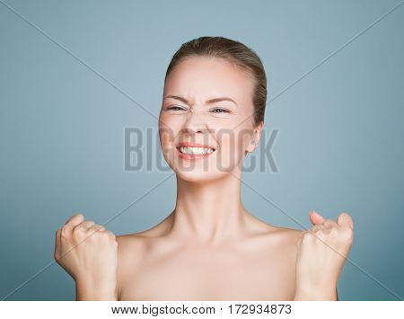 Happy Healthy Model Woman with Perfect Skin on Blue Background. Delight and Luck