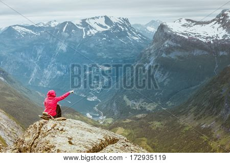 Tourism vacation and travel. Female tourist on Dalsnibba viewpoint pointing with finger on Geirangerfjord and mountains landscape Norway Scandinavia.