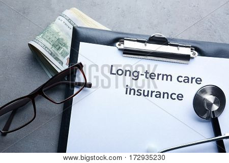 Text LONG-TERM CARE INSURANCE on clipboard with glasses, stethoscope and dollars, closeup