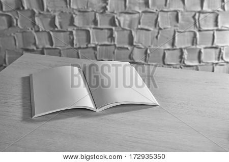 Blank brochure on white wooden table against textured wall