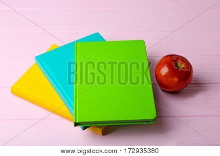 Books and apple on wooden background