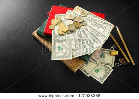 School supplies, dollar banknotes and coins on blackboard. Pocket money concept