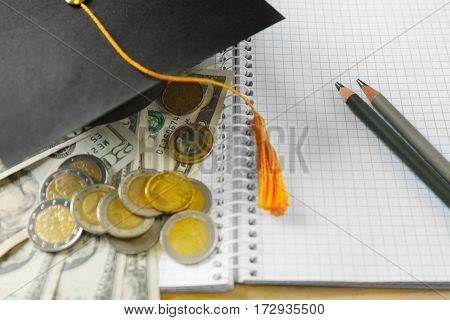 Close up view of school supplies, graduation hat, banknotes and coins. Pocket money concept