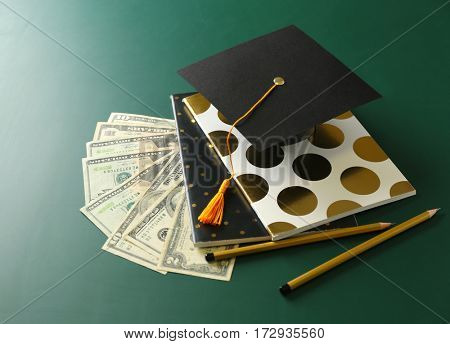 School supplies, graduation hat and dollar banknotes on green background. Pocket money concept