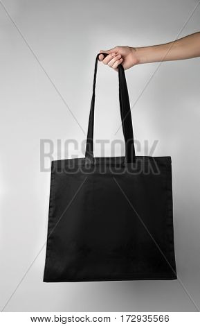 Hand holding textile shopping bag isolated on white