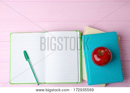 Notebooks and apple on wooden background
