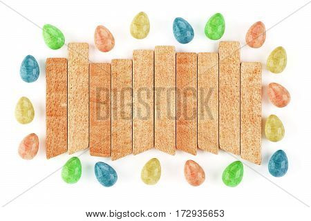 Frame made of easter eggs with wooden plank in middle isolated on white background. 3d rendering