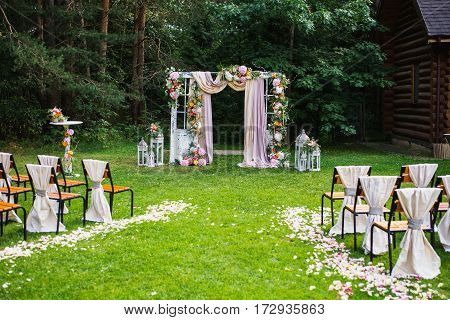 Beautiful rustic wedding ceremony outdoors. Decorated chairs stand on the grass. Wedding arch made of cloth and white and pink flowers on a green natural background. Old doors rustic style. Wedding flowers. Wedding concept