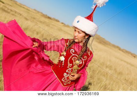 Beautiful kazakh woman in national costume in the steppe dancing with dombyra