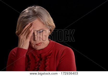 melancholy older woman in red on a black background poster