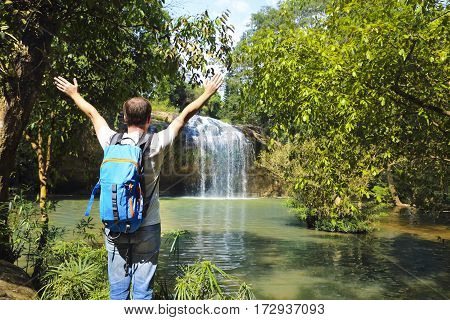 Man with backpack looking at scenic waterfall in Vietnam