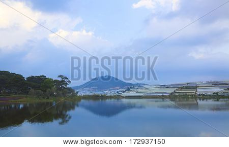 Beautiful view of the valley of agricultural lands and Da Lat city (Dalat) on the blue evening sky background in Vietnam. Da Lat is a popular tourist destination of Asia.