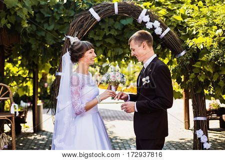 Love of groom and bride in white dress on background of the arch. Wedding photography. A happy family love. To love each other. Strong love