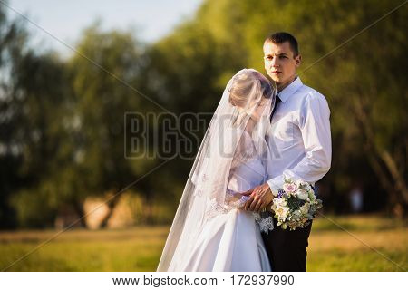Groom and bride in a white wedding dress on a background of nature. Wedding photography. Happy family. Wedding gown and wedding flowers.