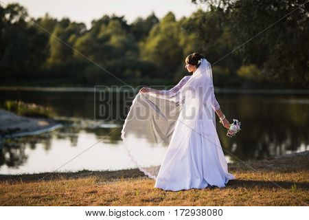 The bride in a white wedding dress on nature background. Wedding photography. Dress on woman. Wedding gown
