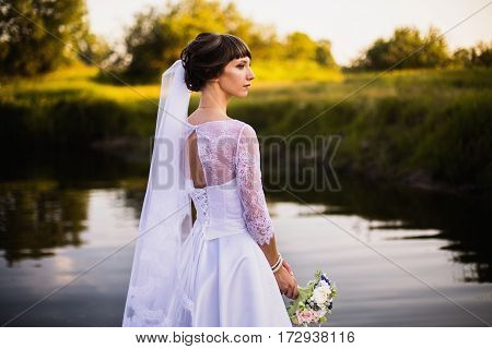 The bride in a white wedding dress on nature background. Wedding photography. Dress on woman. Bride in wedding gown